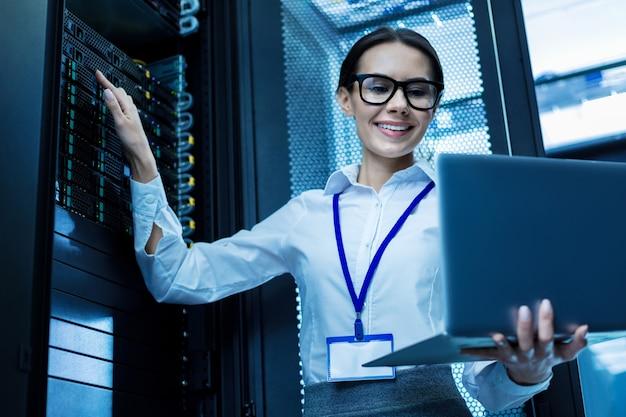 Meu melhor dia. mulher atraente contente trabalhando em um gabinete de servidor e segurando seu laptop