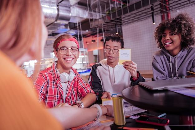 Meu prazo. homem jovem satisfeito sentado entre seus amigos enquanto jogam um jogo de mesa juntos
