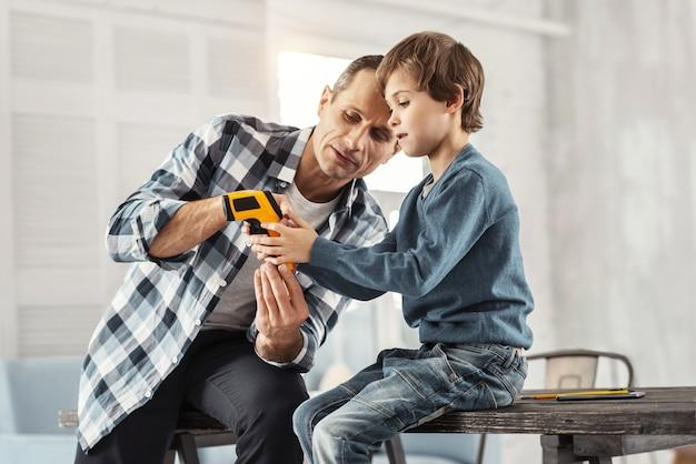 Meu querido menino. homem sério atraente de cabelos escuros mostrando instrumentos para o filho enquanto está sentado na mesa e o filho dele sentado perto dele
