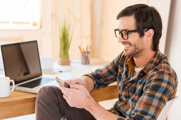 Meu smartphone está sempre à mão. jovem alegre segurando um telefone celular e digitando uma mensagem enquanto está sentado em seu local de trabalho