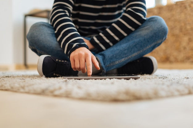 Meu tablet. adolescente vestindo roupas casuais e tênis, sentado no chão e tocando seu moderno tablet digital sensível ao toque