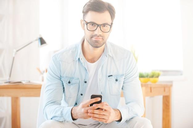 Meu trabalho é minha vida. jovem bonito de camisa e óculos, segurando um telefone celular e olhando para a câmera enquanto está sentado em frente ao seu local de trabalho