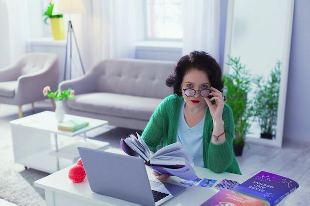 Meu trabalho. mulher séria e inteligente sentada em seu escritório enquanto trabalha como astróloga