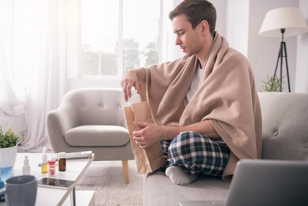 Meu tratamento. homem bonito e doente sentado no sofá enquanto tira o remédio da sacola