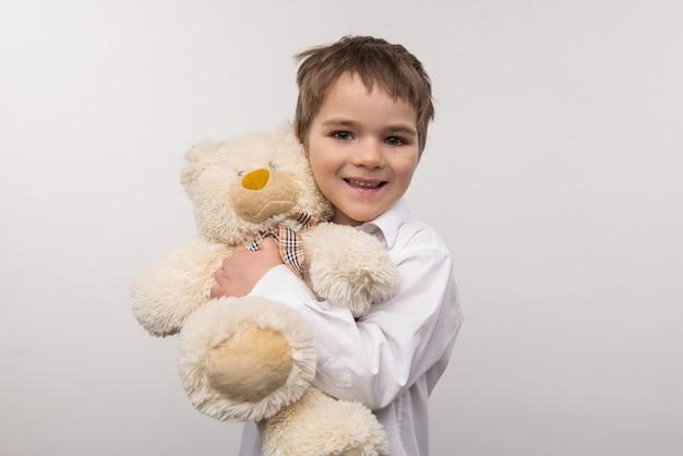 Meu urso fofo. bom garoto encantado abraçando seu urso enquanto olha para você
