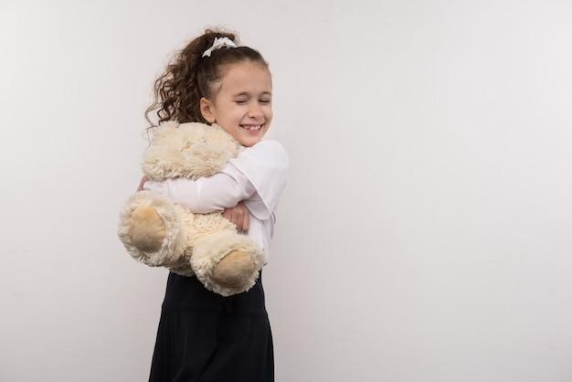 Meu urso. jovem feliz abraçando seu brinquedo em pé contra um fundo branco