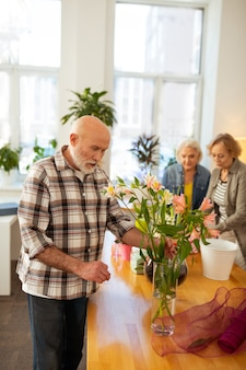 Meus favoritos. homem de cabelo grisalho positivo sorrindo enquanto admira lindas flores