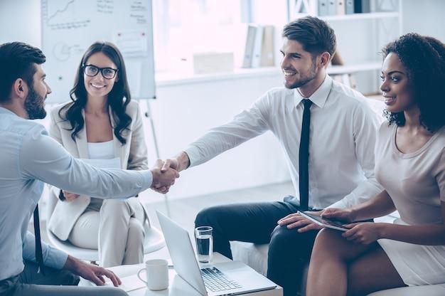 Meus parabéns! dois homens bonitos apertando as mãos com um sorriso enquanto estão sentados no sofá do escritório com suas belas colegas de trabalho