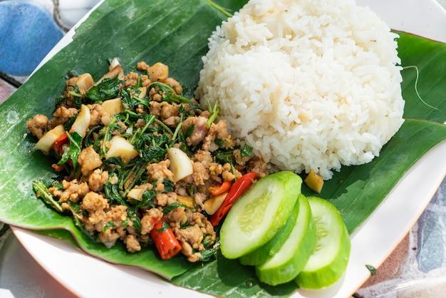Mexa a carne de porco picada frita e o manjericão com o arroz. estilo de comida de rua tailandesa