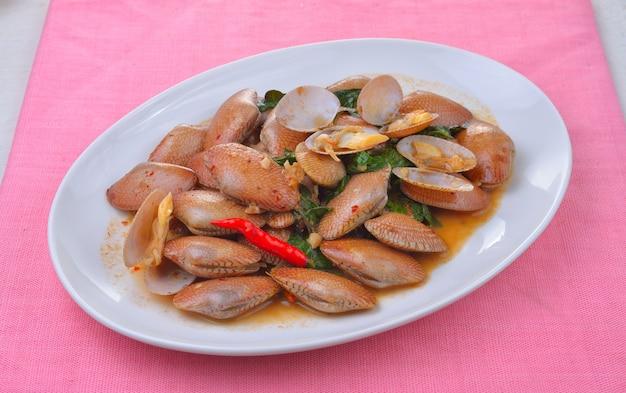 Mexa amêijoas fritas com pasta de pimentão assado e folhas de manjericão tailandês