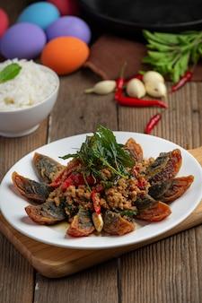 Mexa basil fried com spicy century egg servido com arroz cozido no vapor e molho de peixe de pimenta, comida tailandesa.