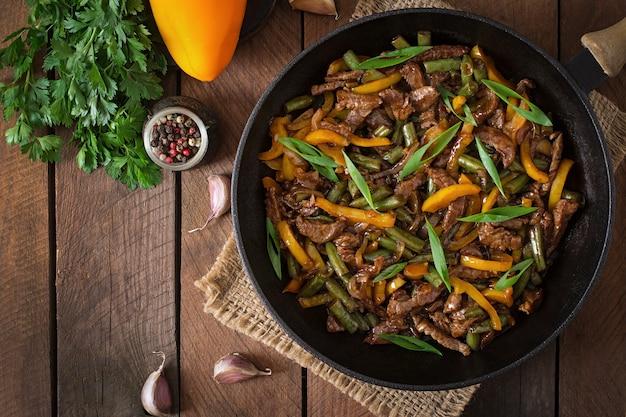 Mexa fritar carne com pimentão e feijão verde