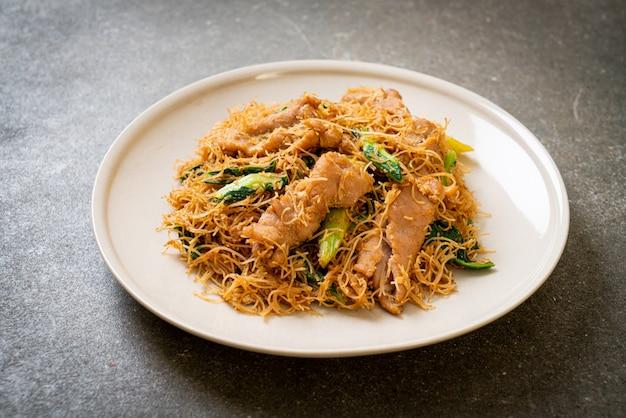 Mexa macarrão de arroz frito com molho de soja preto e carne de porco