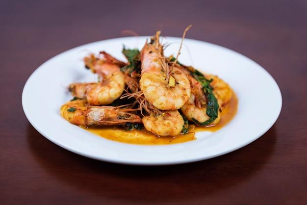 Mexa o curry vermelho frito com camarão comida tailandesa em um fundo de madeira