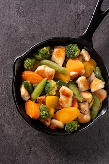 Mexa o frango frito com legumes em uma panela de ferro