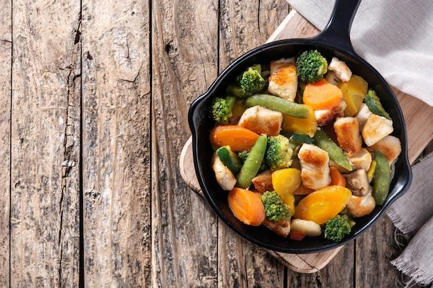 Mexa o frango frito com legumes na panela de ferro na mesa de madeira