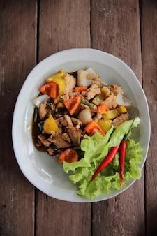 Mexa o frango frito com pimenta-do-reino no fundo de madeira
