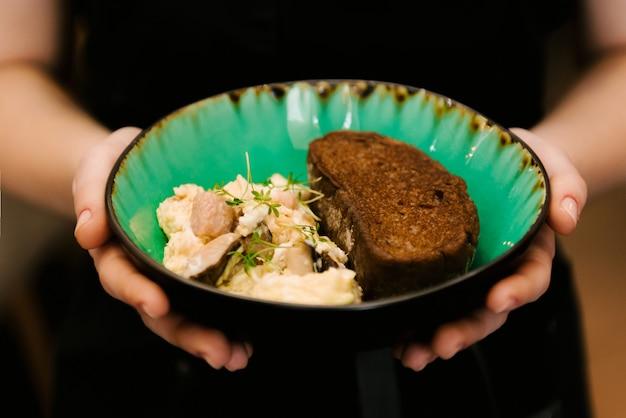 Mexa o prato de ovos e pão na mão, foco seletivo