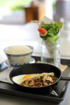 Mexa porco frito e manjericão servido com arroz e ovo frito, comida tailandesa