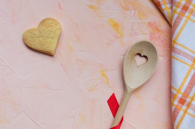 Mexendo a colher e o biscoito de manteiga em forma de coração
