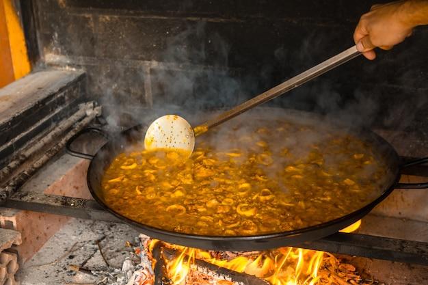 Mexendo o arroz da paella valenciana com brasas e legumes