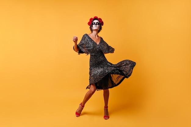 Mexicano bronzeado bem construído em um vestido brilhante com decote danças incendiárias no feriado nacional com máscara em forma de caveira na parede isolada