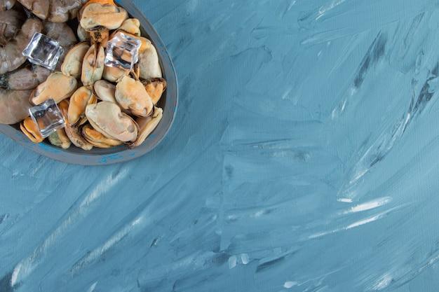 Mexilhões, camarões e cubo de gelo em uma placa de madeira, no fundo de mármore.