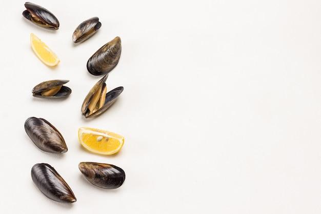 Mexilhões com conchas abertas e limão em fundo branco. frutos do mar de marisco. postura plana.