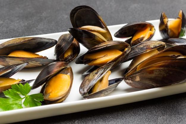 Mexilhões com conchas abertas na chapa branca. frutos do mar de marisco. fechar-se. vista do topo.
