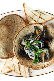 Mexilhões com molho em uma tigela. cozinha mediterrânea deliciosa e saudável. vertical. fechar-se.