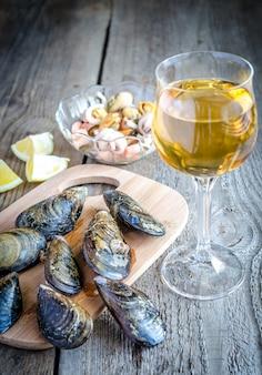Mexilhões com um copo de vinho branco na mesa de madeira