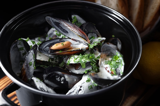 Mexilhões cozidos com molho em uma panela preta