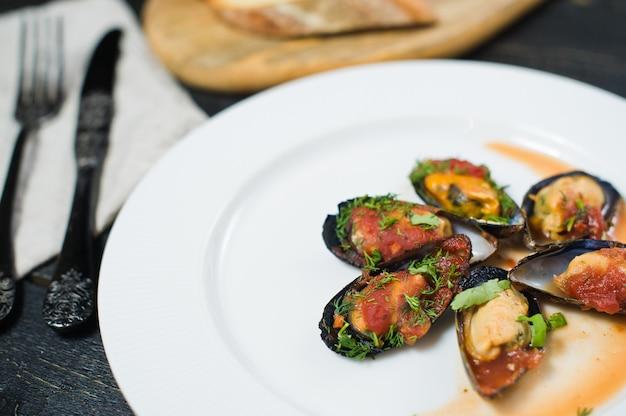 Mexilhões cozidos no molho de tomate com coentro e parmesão em uma placa branca.