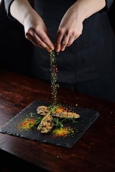 Mexilhões cozidos sob queijo com pinhões. em um quadro negro