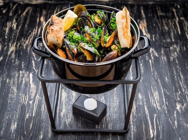 Mexilhões em metal cozinhar prato e baguete francesa com ervas