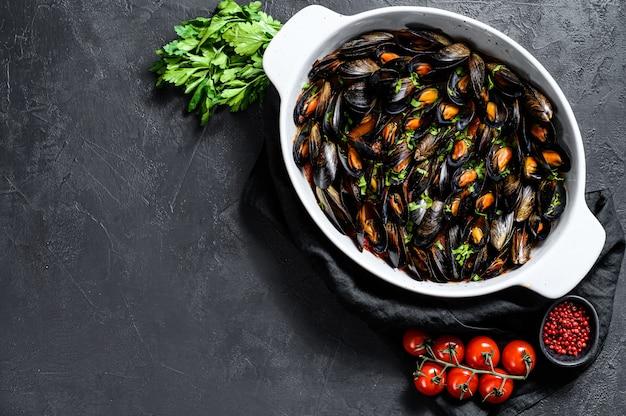 Mexilhões em molho de tomate com salsa e ervas. fundo preto. vista do topo. espaço para texto