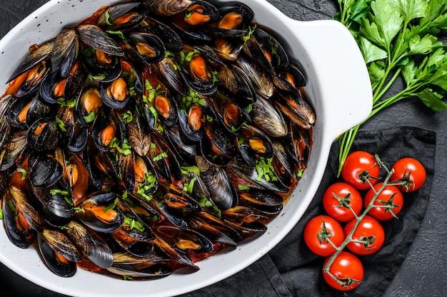 Mexilhões em molho de tomate com salsa e ervas. fundo preto. vista do topo