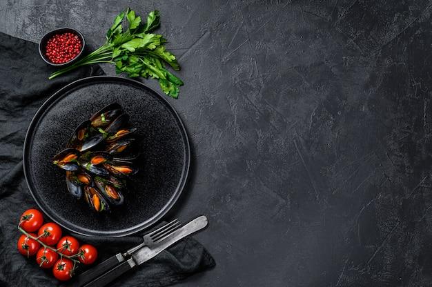 Mexilhões em molho de tomate, decorado com salsa e tomate cereja. fundo preto. vista do topo. espaço para texto