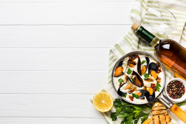 Mexilhões flat-lay em molho branco e vinho na toalha de mesa com copyspace
