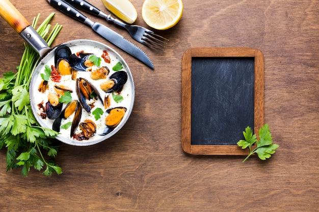 Mexilhões flat-leigos em molho branco na toalha de mesa com quadro-negro