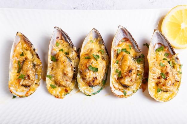 Mexilhões greenshell cozidos em meia casca com queijo, salsa e limão em um prato branco. aperitivo quente tradicional. close-up, vista de cima.