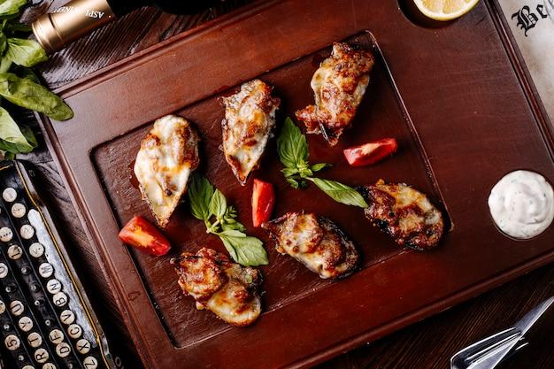 Mexilhões grelhados com queijo derretido na parte superior, hortelã e tomate em uma placa de madeira marrom.