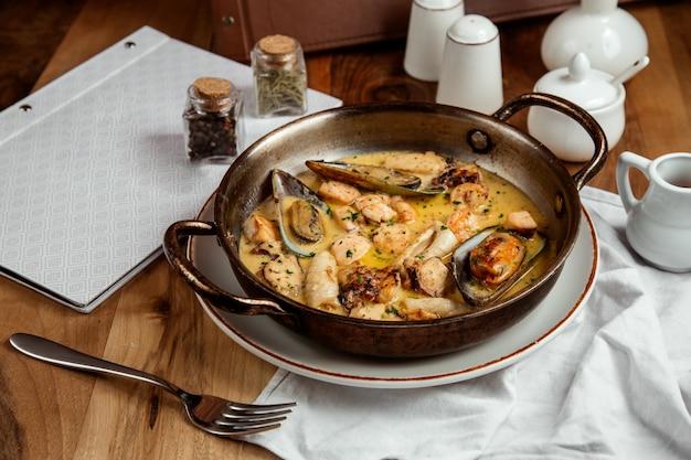 Mexilhões grelhados com vieiras ervas molho de manteiga sal e pimenta na mesa