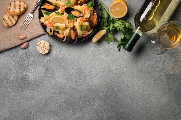 Mexilhões, pão torradas e vinho branco na mesa de pedra. vista superior com espaço de cópia.