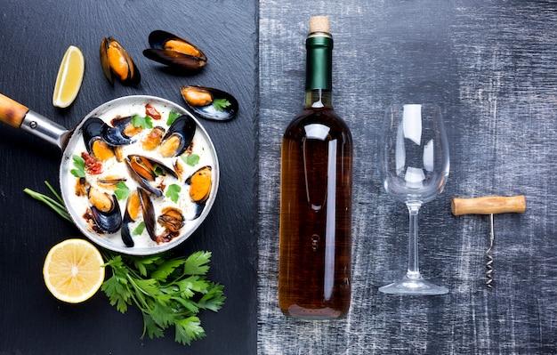 Mexilhões planos em molho branco e garrafa de vinho