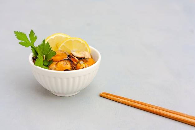 Mexilhões sem casca com rodelas de limão em tigela de cerâmica Foto Premium