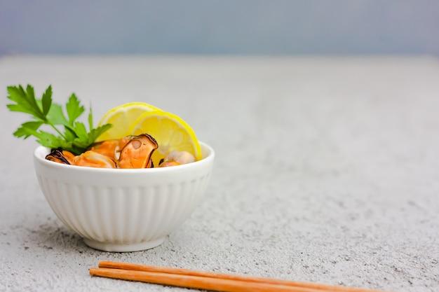 Mexilhões sem casca com rodelas de limão em uma tigela de cerâmica branca. Foto Premium