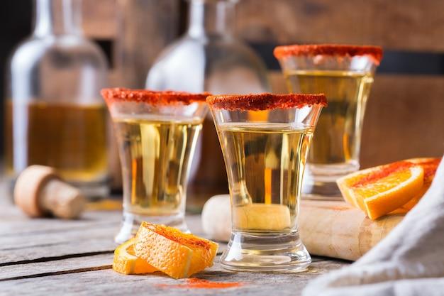 Mezcal mexicano ou mescal com pimenta malagueta e uma rodela de laranja. bebida alcoólica semelhante à tequila