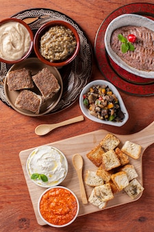 Meze é um conjunto oriental de aperitivos servidos em tigelas com babaganoush, requeijão, homus, muhammara e quibe