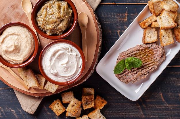 Meze é um conjunto oriental de aperitivos servidos em tigelas com babaganush, requeijão, homus e quibe